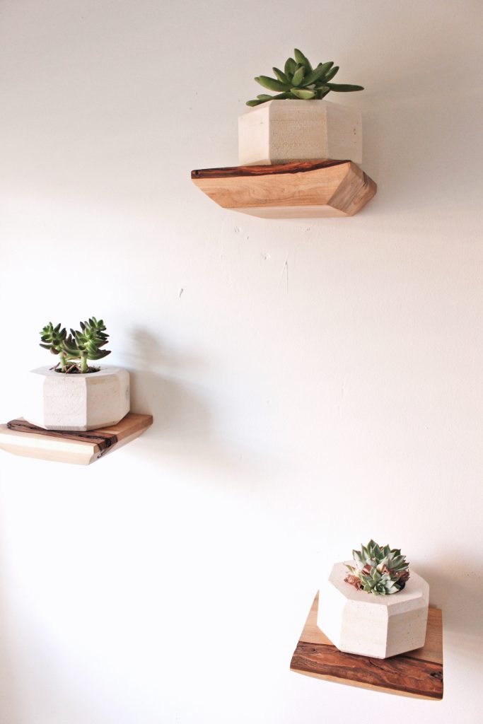 Beautiful floating shelves made out of cherry wood and featuring a live edge for a stylish, minimalist, and rustic design.